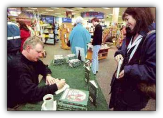 Image: Author John Snyder signs a book for a customer at Borders Books.