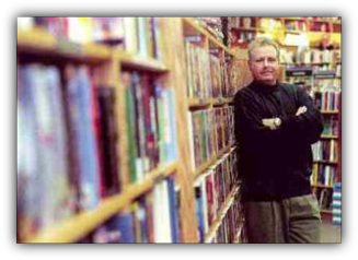 Image: Author John Snyder taking a break from a book signing and leaning against a shelf of books at Borders Books.
